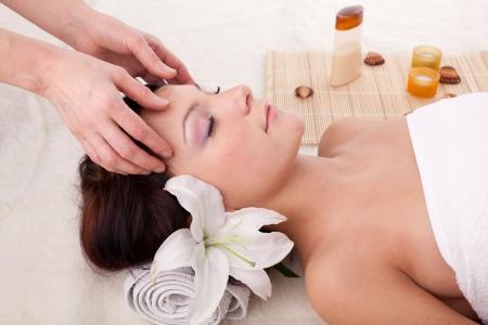 masajes faciales: Joven y bella mujer recibiendo tratamiento de spa sobre un fondo blanco