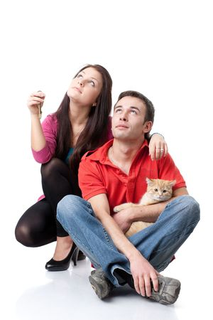 The young happy family with kitten and house keys in hands on a white background. House purchase concept. photo