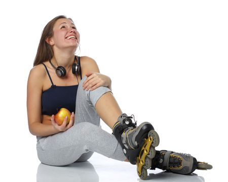The beautiful girl  in rollerskates with an apple on a white background. photo