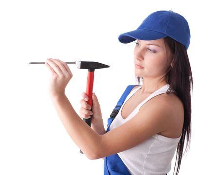 Young woman in overalls with hammer and nail on a white background. photo