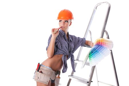 Young woman in hardhat with a color guide and paintbrush on a white background. Stock Photo - 6752581