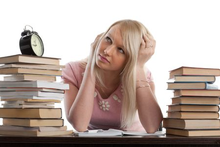 Stressed young woman  at a desk among books on a white background photo