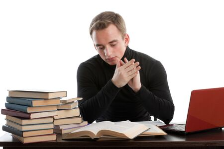 Stressed young man sitting at a table among books and  laptop on a white background photo