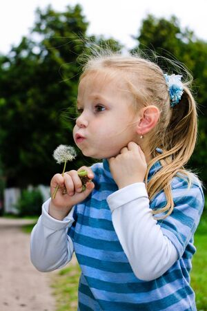 Cute little girl blowing  on a dandelion in the park photo