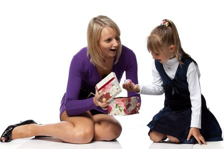 Young mother and her daughter with gift box on a white background. photo