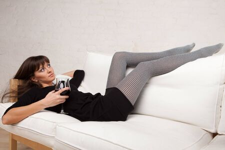 Young woman relaxes at home on the white sofa with a glass of red wine Stock Photo - 6814246
