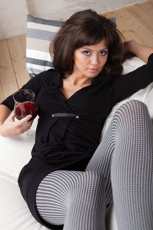 relaxes: Young woman relaxes at home on the white sofa with a glass of red wine