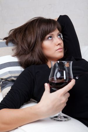 Young woman relaxes at home on the white sofa with a glass of red wine photo
