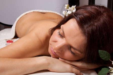 Young beautiful woman on massage procedure in spa salon photo