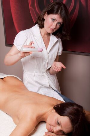 The nice female masseur carries out massage procedure in spa salon. Stock Photo - 6814243