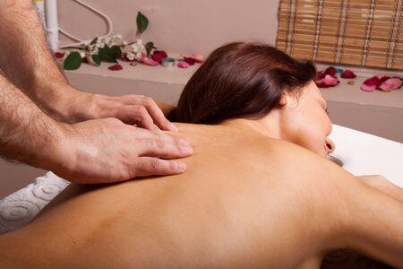 Young beautiful woman on massage procedure in salon photo