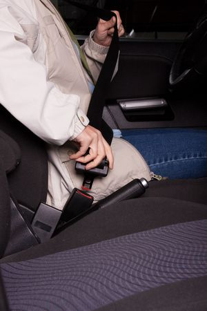 Female hand  fastening  a seat belt in the car.