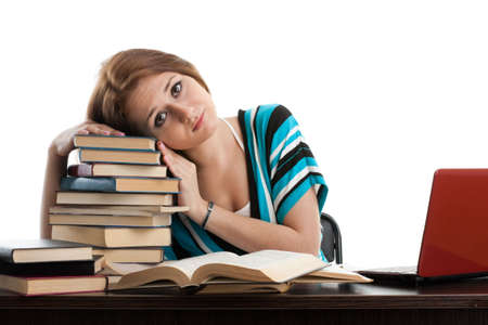 Stressed young woman sitting at a table among books and  laptop on a white background photo
