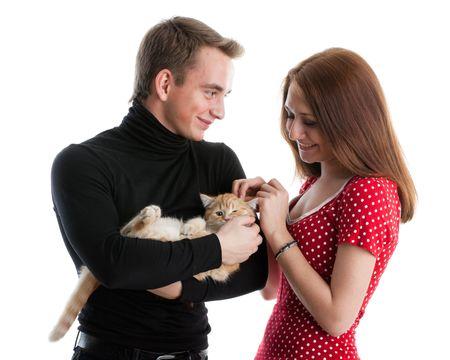 amusant: Le jeune couple heureux avec un petit chaton amusante sur un fond blanc.  Banque d'images