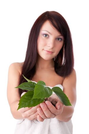 The beautiful young woman holding a green plant in the hands on a white background. Concept of protection of environment. photo