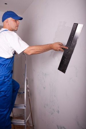 Male builder makes repairs in the apartment photo