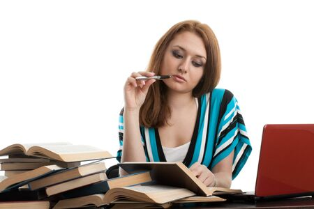 Young woman sitting at a desk   among  books and laptop on a white background. photo