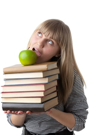 Young beautiful woman with books and apple on a white background. Student. Stock Photo - 7002143