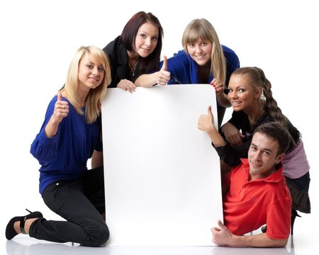 The group of young people holds the empty board for the text on a white background. 免版税图像