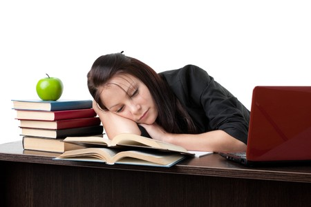 Stressed young woman sleeping at office desk photo