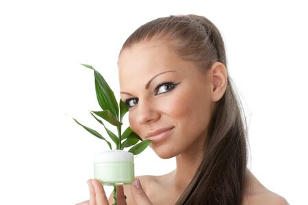 The attractive young woman with a branch of a bamboo and a cosmetic cream on a white background photo