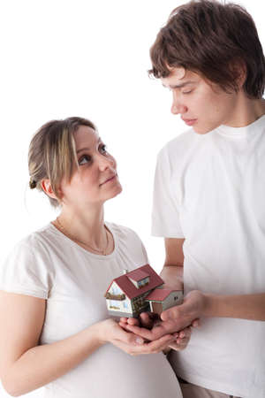 The young happy pregnant family  holds house model in hands on a white background. House purchase concept. photo