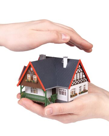 Hands with model of house on a white background. Concept  of buying and insuring  real estate. photo