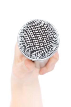 Silver microphone in a female hand on a white background. photo