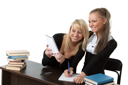 Two girlfriends of the student prepare for examination, sitting at a desk on a white background. photo