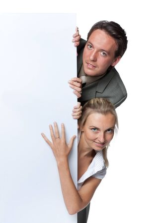 Pretty businesswoman and businessman hold an empty billboard over white background. Stock Photo