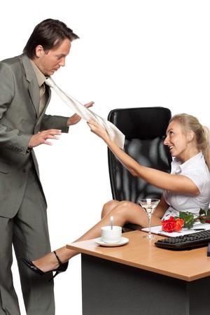seducing: Molestie sessuali. Piuttosto businesswoman, disegna il dipendente per la sua cravatta su uno sfondo bianco.  Archivio Fotografico