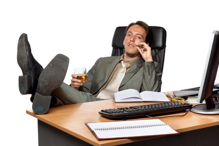 stern: Businessman with cigar and glass of whisky  on workplace  on a white background. Stock Photo