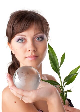 The beautiful young woman holding a green plant and globe in the hands on a white background. Concept of protection of environment. photo