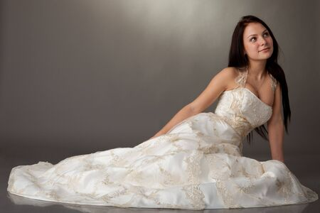 The beautiful young woman in a wedding dress on a grey background. photo