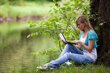 The beautiful young woman sits on a grass in park with the laptop. photo