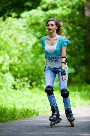 The beautiful young woman rollerskating in park. Stock Photo - 7131152