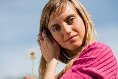 The beautiful young woman with dandelion before the background of blue sky. photo