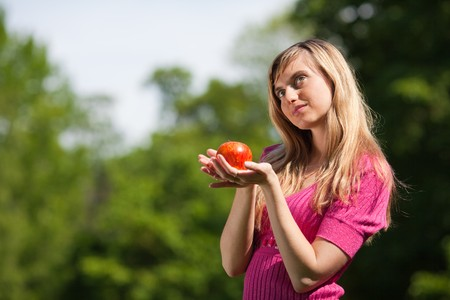 The beautiful young woman with a red apple in the park.  Concept of healthy lifestyle. photo