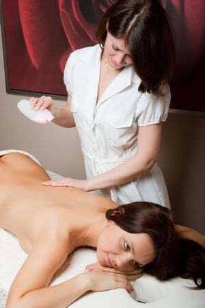 The nice female masseur carries out massage procedure in spa salon. photo