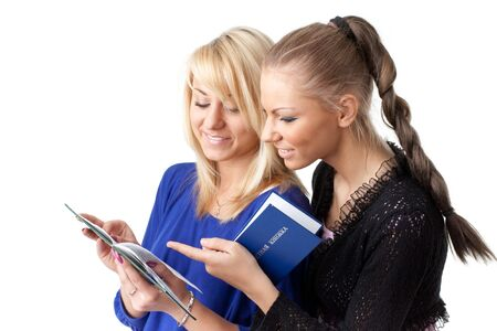 Two girlfriends with the record book on a white background.  Students. photo