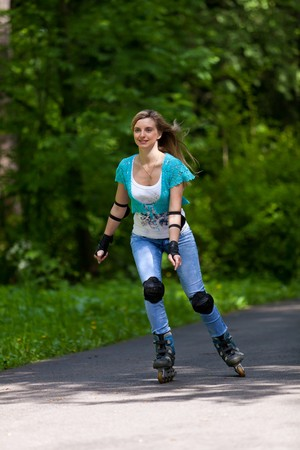 The beautiful young woman rollerskating in park. Stock Photo