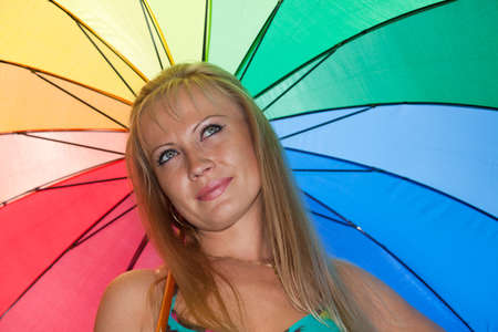 Portrait of the beautiful young woman with a multi-coloured umbrella. Stock Photo - 7295366
