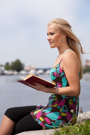 The beautiful young woman sits on a grass in park with the book. Stock Photo - 7295358