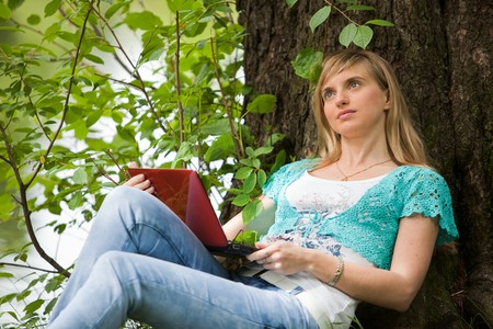 The beautiful young woman sits on a grass in park with the laptop. Stock Photo - 7310824