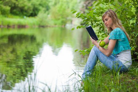 lectura y escritura: La joven y bella mujer se sienta sobre un c�sped en el parque con el libro y una manzana.