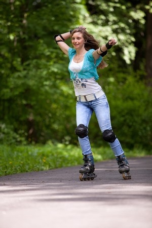 The beautiful young woman rollerskating in park. photo