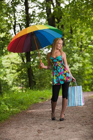 Happy young woman with shopping bags and umbrella goes home after successful shopping. Outdoors. photo