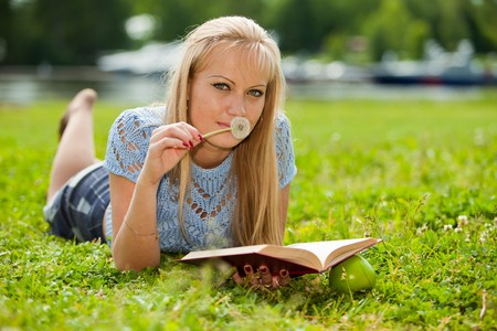 The beautiful young woman  lies on a grass in park with the book and a dandelion. photo