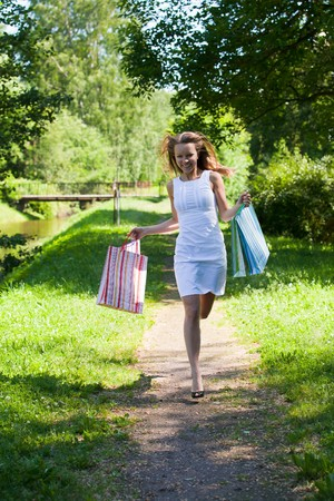 Happy young woman with shopping bags goes home after successful shopping. Outdoors. photo