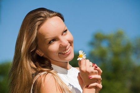 fortunetelling: The beautiful young woman with camomile  against of blue sky. Fortune-telling on a camomile. Stock Photo